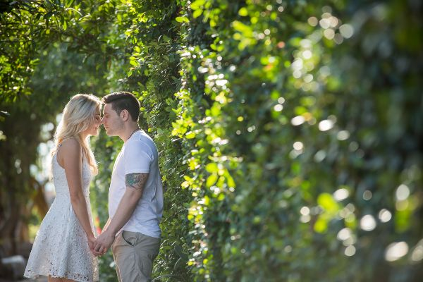 Bride and groom standing facing each other, heads together and hands held, in casual attire and standing beside beautiful green hedge. Photographed by Newcastle and Hunter region wedding photographer.