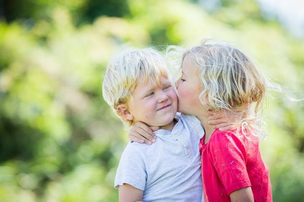 Young siblings give each other a kiss in this bright family portrait. Set outside with the children in focus and out of focus greenery in the background.