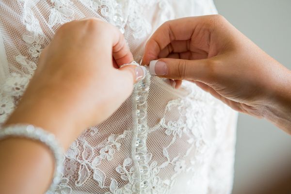 Picture of back of bride's white lace dress being fastened with buttons.