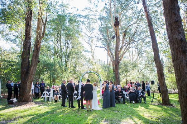 Wedding ceremony amongst tall trees of Hunter Valley with bride and groom standing under arch and family and friends gathered