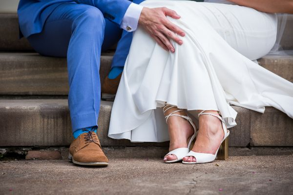 Photograph of Maitland bride and room on steps; the trousers and bottom of dress and shoes are visible with the groom's hand on the bride's knee.