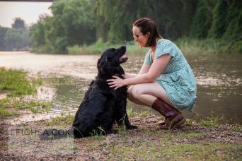 mans best fried, woman with her beautiful black labrador near the twinkly river